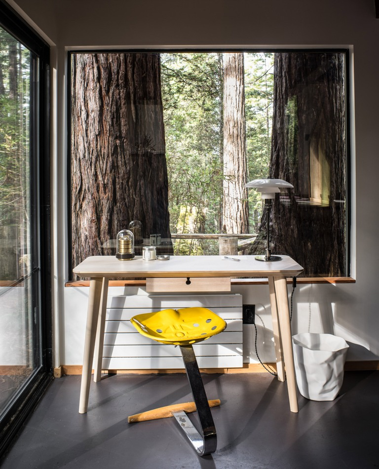 The home office features a mid-century modern desk and a bright stool, there are openings outside everywhere
