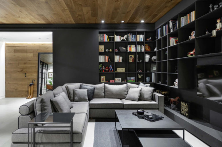 The living room features a lot of black bookshelves, a large corner sofa and some coffee tables plus a wood clad ceiling
