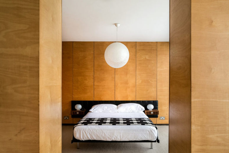 The master bedroom is clad with light-colored plywood, there's a comfy bed and a couple of wardrobes
