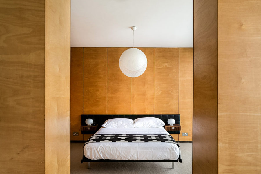 The master bedroom is clad with light colored plywood, there's a comfy bed and a couple of wardrobes