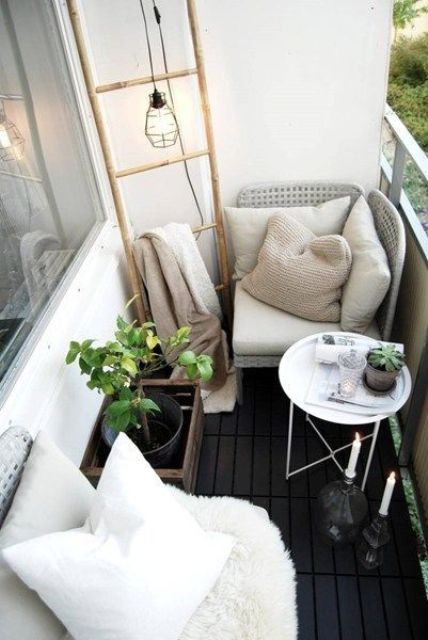 a black and white balcony with two comfy wicker seats, a coffee table, candles and a ladder for storage