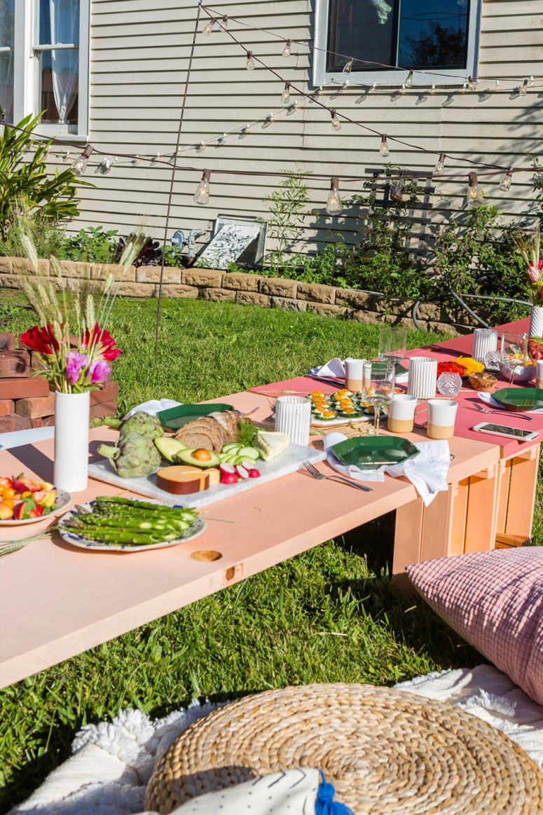 a colorful backyard floor table made of 8 IKEA Knagglig boxes is a bright touch to your outdoor space