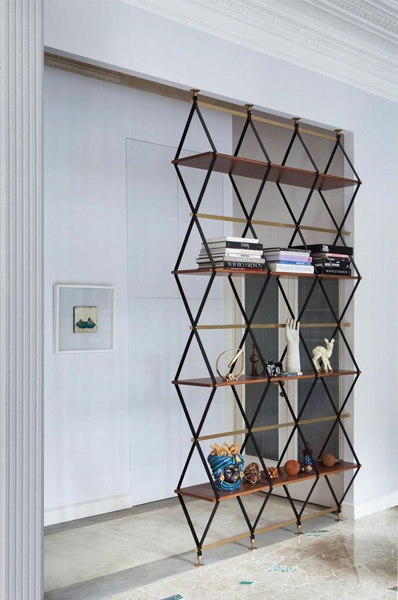 a floor to ceilinglightweight shelving unit separates the entryway from the living room