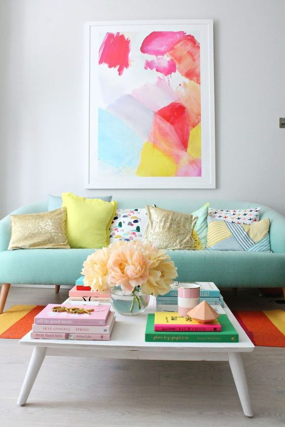a mint sofa is a soft base for adding bright colors with the rug and the artwork for a cheerful feel