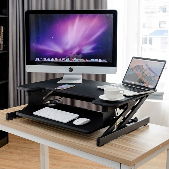 a small black height adjustable sit-stand desk with a keyboard tray for any office