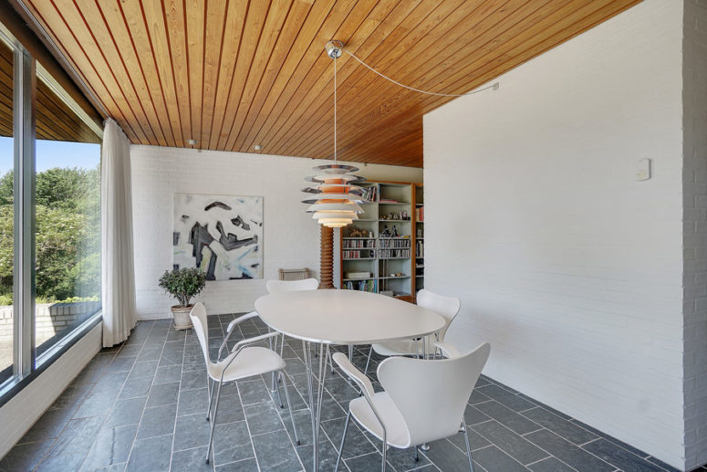 The fireplace wall hides the dining zone with a white dining set and a cool view