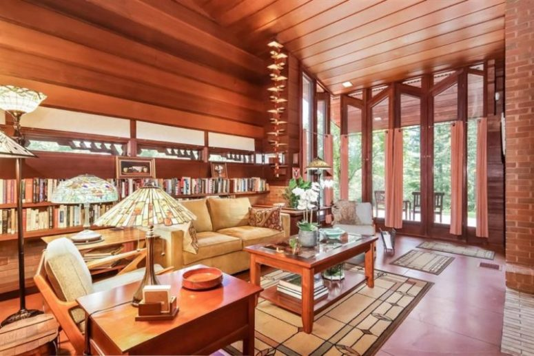 The living room features high ceilings, a glazed wall, lots of bookshelves and a selection of red wood furniture