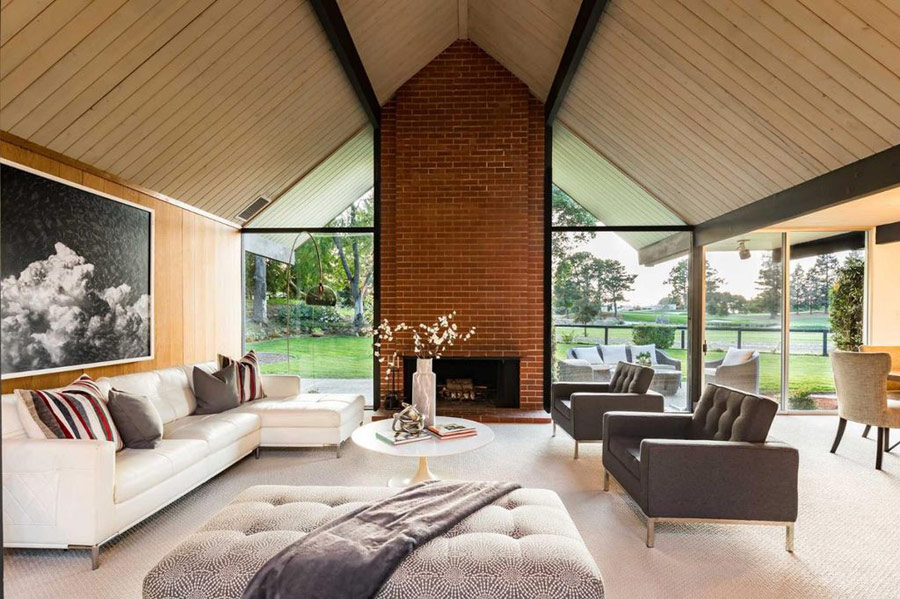 The living room is done with a glazed wall, a brick clad fireplace and a selection of comfortable and chic furniture