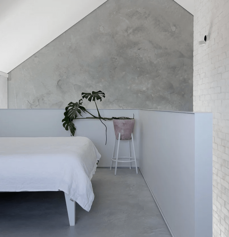The master bedroom is done with concrete and brick walls, a lilac half wallm which adds color and a lilac planter