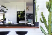 03 a black and white space with a dark stained bar counter and black metal stools plus cacti
