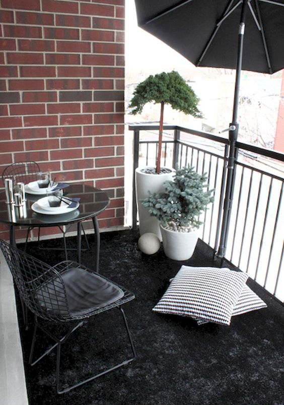a black rug, a metal dining set, potted plants and a large umbrella for privacy and to protect from the sun