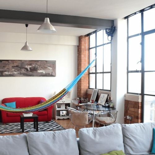 a colorful hammock is a fun and relaxed touch to a plain and usual space