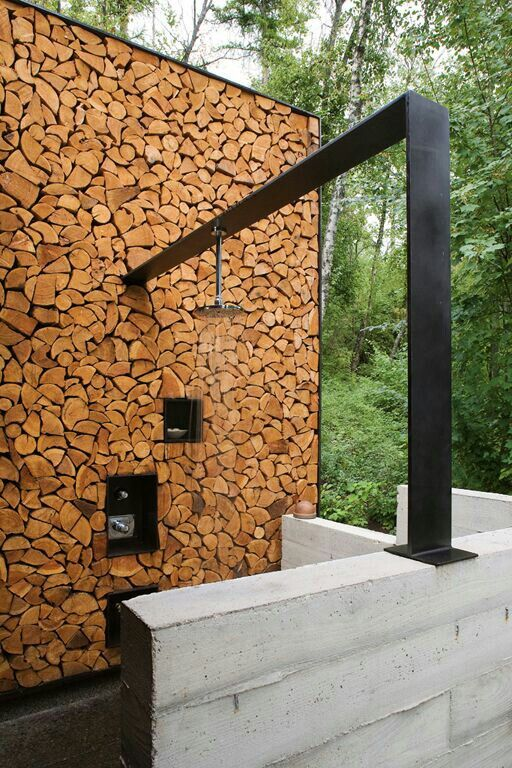 a contemporary rustic outdoor shower with a firewood wall and a dark metal panel