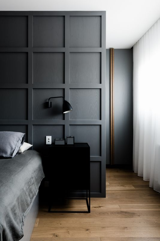 a graphite grey molded statement wall accentuates the bed instead of a headboard