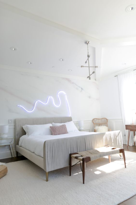 a neon light piece over the bed is a great idea to spruce up the space and make it modern and bold