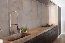 03 an industrial kitchen with dark metal cabinets and a concrete countertop plus a backsplash
