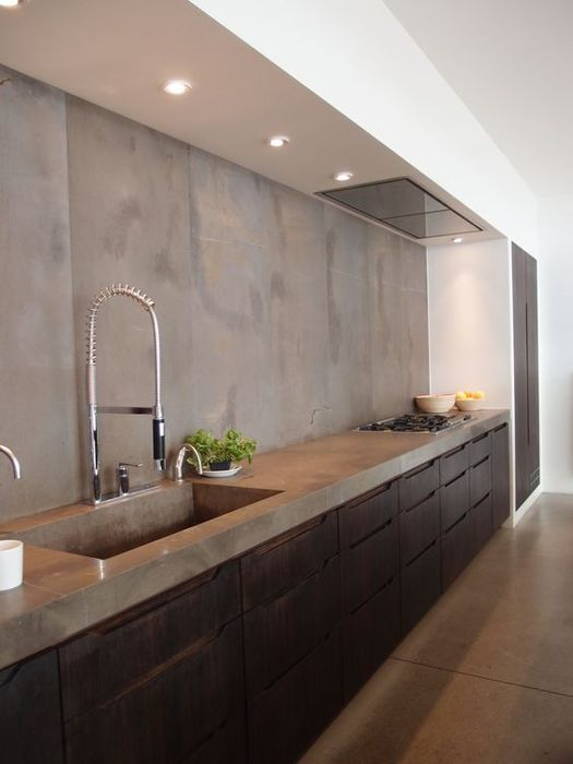 an industrial kitchen with dark metal cabinets and a concrete countertop plus a backsplash