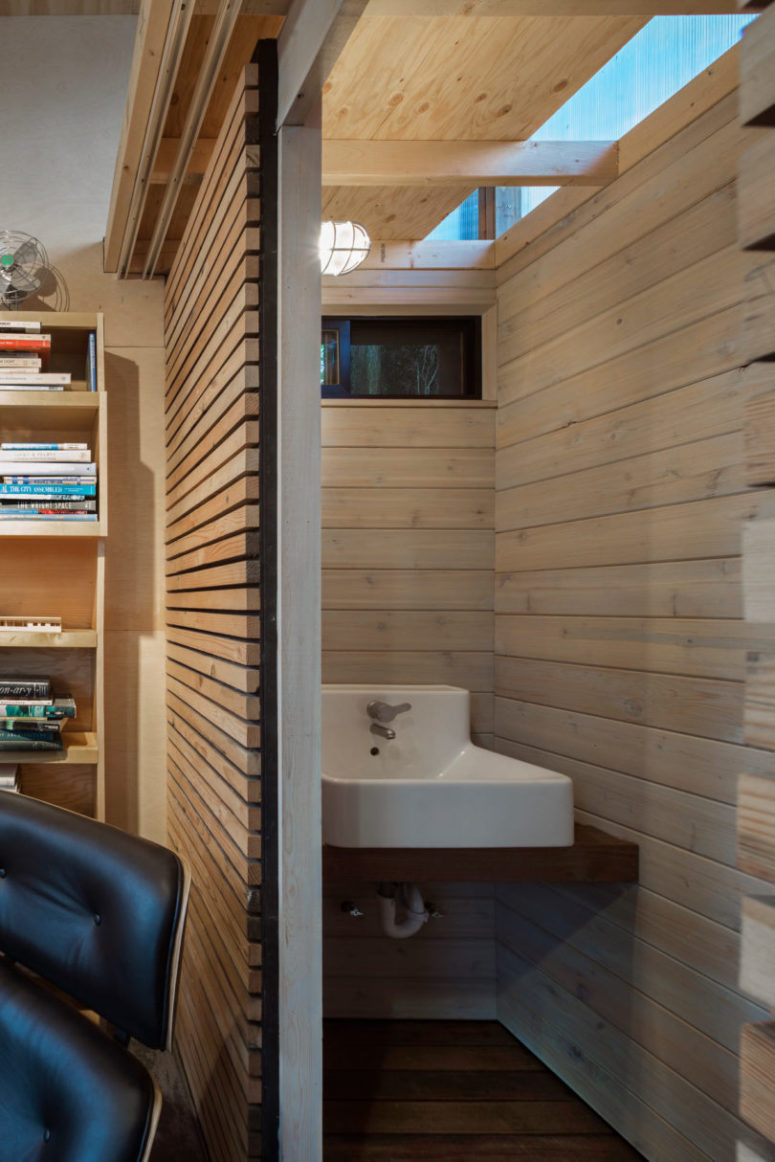 Inside there a tiny powder room all clad with light-colored wood for a rustic feel