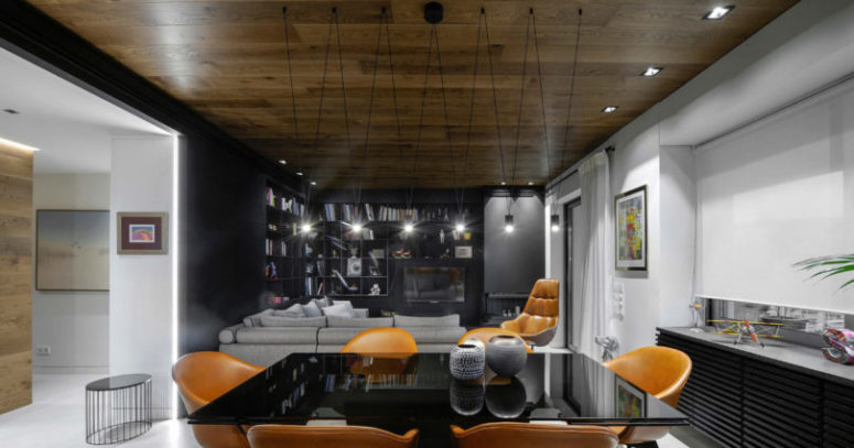 The dining space features a black table with a glass top and amber leather chairs