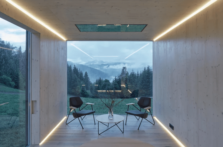 The interior is minimalist, everything is clad with light-colored wood, there are built-in lights and comfortable furniture