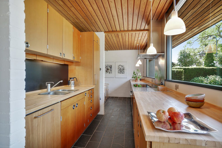 The kitchen is done with light-colored wooden cabinets, and there's a breakfast zone further