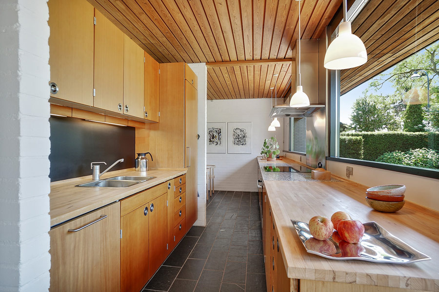 The kitchen is done with light colored wooden cabinets, and there's a breakfast zone further