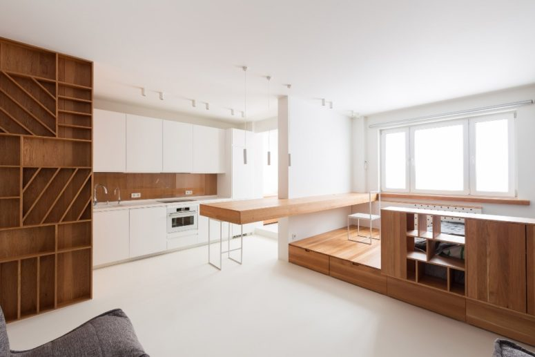 The kitchen is further, with a large table coming on both sides of the wall to use it for work and eating