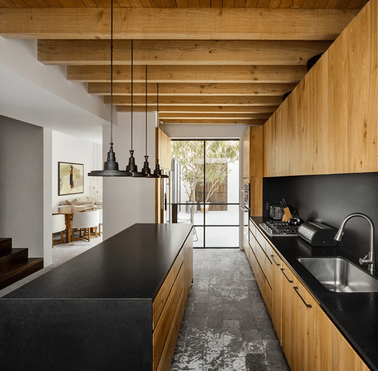 The kitchen was done with dark metal and light-colored wood for a strong contrast