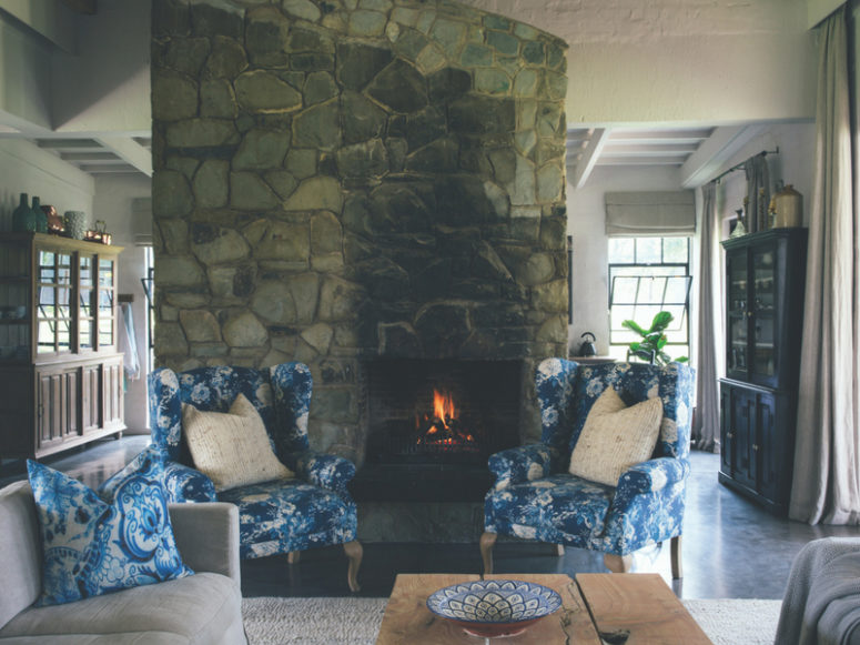 The living room features a cozy hearth clad with stone and some vintage-inspired furniture