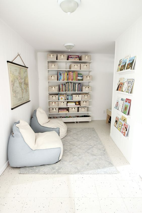a chic kids' reading nook with lots of books and a couple of cream and blue bean bag chairs