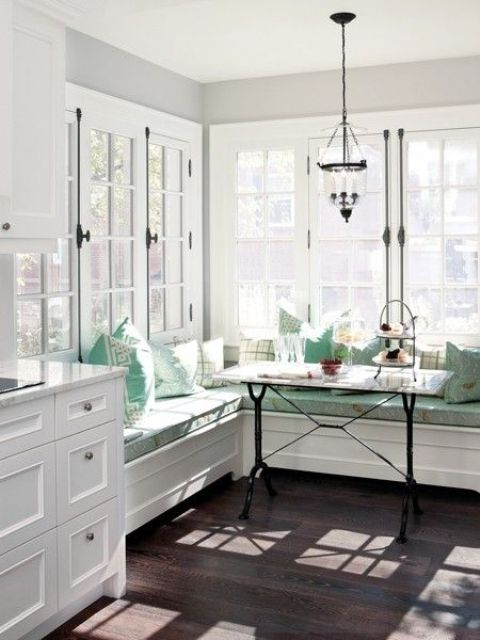a coastal kitchen and dining space with a banquette seating in aqua shade