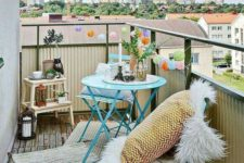 04 a colorful balcony with bright blue furniture, a ladder, candle lanterns and rugs