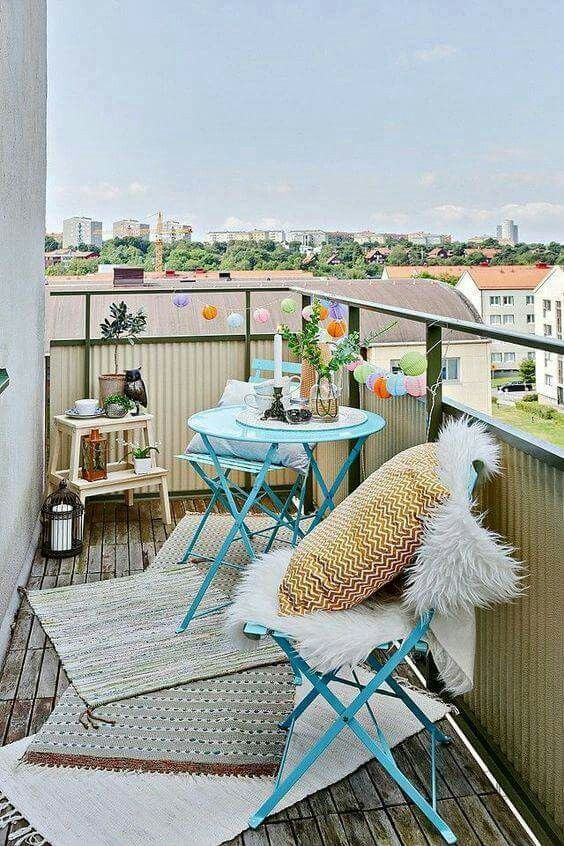 a colorful balcony with bright blue furniture, a ladder, candle lanterns and rugs