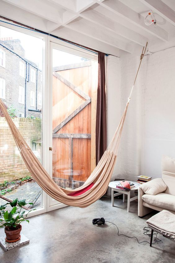 a contemporary to industrial space is done with a beige hammock by an entry to a private courtyard