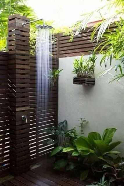 a gorgeous outdoor shower clad with dark stained wood and lots of potted plants plus a rain shower