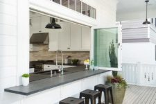 04 a kitchen pass through is fitted with glass folding windows fitted with a black bar lined with black stools