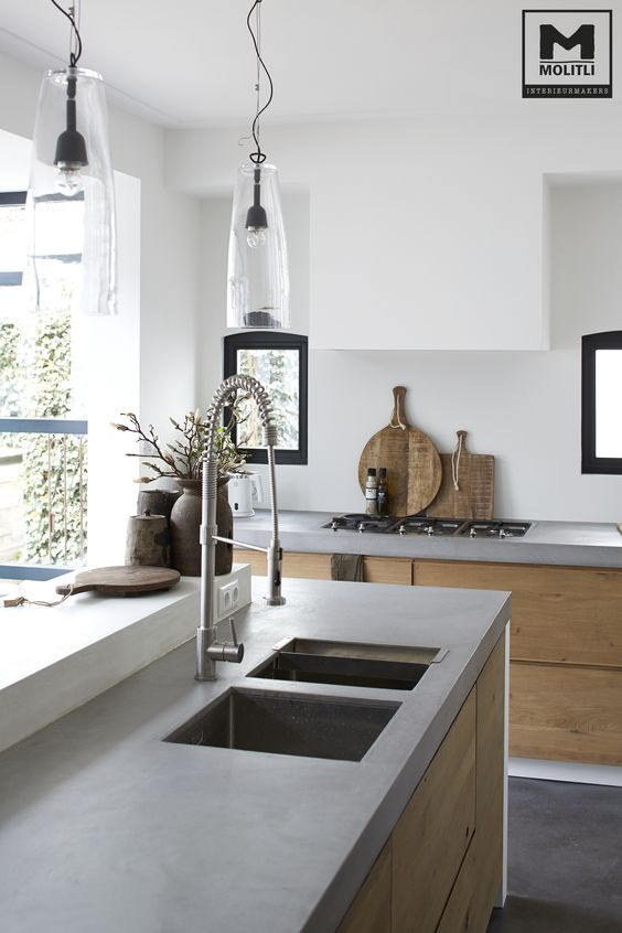 a serene contemporary space with light colored wooden cabinets, upper white ones and concrete countertops