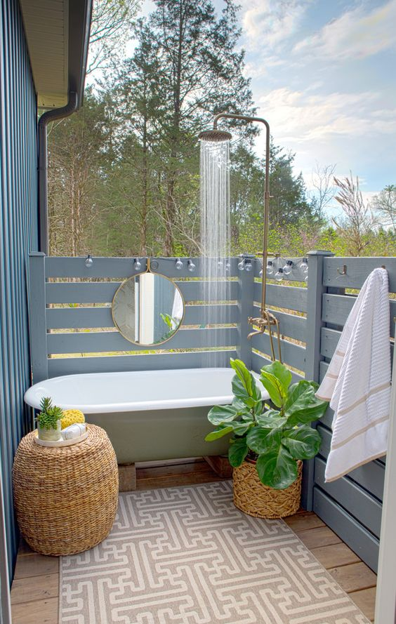 an outdoor bathtub plus a shower, wicker planters and a table and powder blue wooden planks all around for privacy