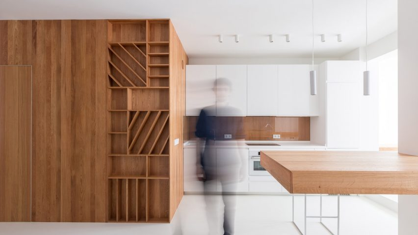 The bathroom is hidden inside a large wooden cube with much storage