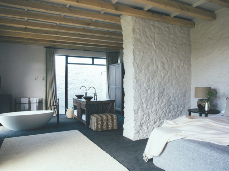 The bedroom includes a bathroom, there's much stone clad and a large double wooden vanity