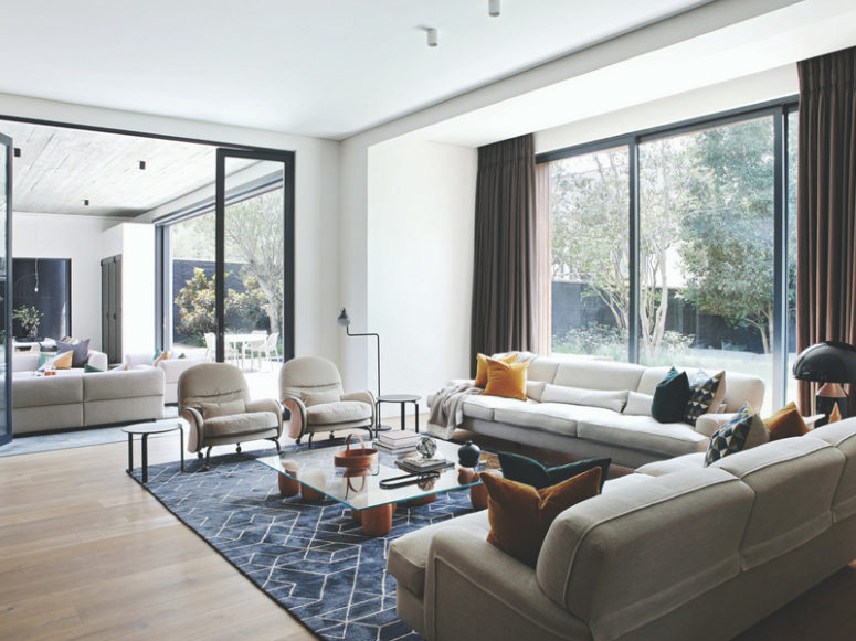 The living room is done with a panoramic window, and glass doors separate the living and dining spaces