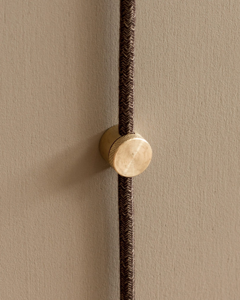 This brass detail on the cord keeps it next to the wall to avoid any mess