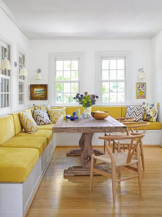 a colorful dining room with a bright yellow corner velvet banquette seating