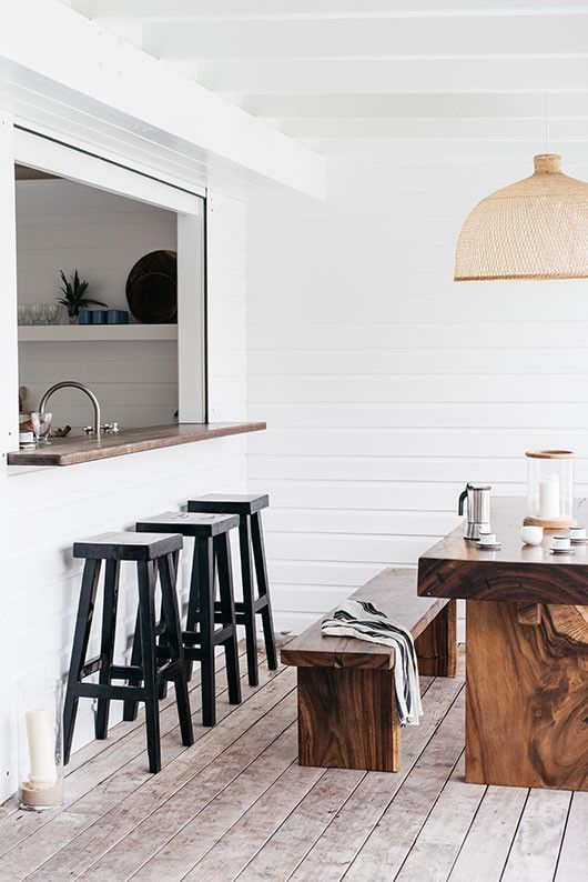 a minimalist space with a kitchen window, a concrete bar counter and tall black stools