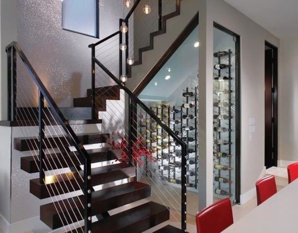 a modern small wine cellar under the stairs with wall mounted metal shelves