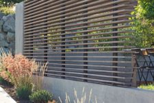 05 a modern wooden beam privacy screen with a concrete base looks ideal for a contemporary space