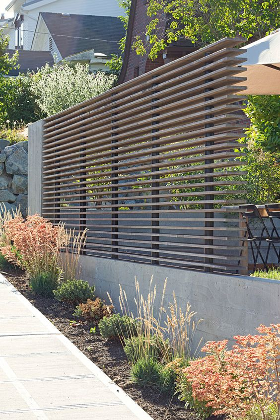 a modern wooden beam privacy screen with a concrete base looks ideal for a contemporary space