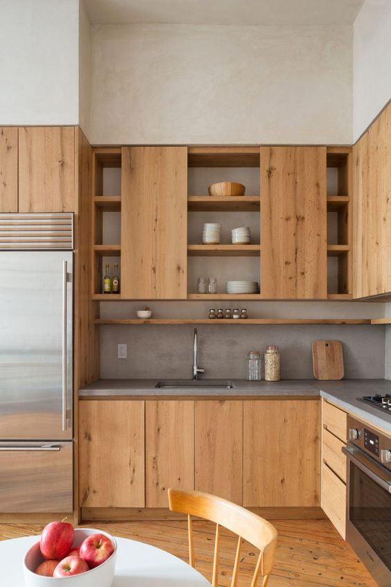 a natural contemporary space with light-colored wooden cabinets and concrete countertops plus backsplashes