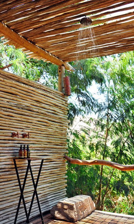 a wooden deck and walls and a roof made of wood sticks, a rain shower plus a small table with shampoos
