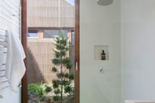 The bathroom features a floor to ceiling window door and a bright green floor in the shower